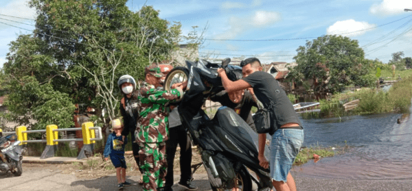 Aksi Babinsa Mempawah Hilir Saat Warga Melintasi Banjir